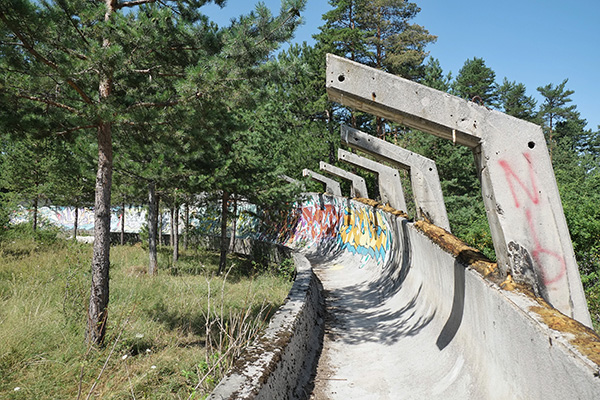 Photo: Gabriel Hess on Flickr | Sarajevo Bobsleigh Track. The bobsleigh ttrack from the Olympic Winter Games in 1984 on Mount Trebevic above Sarajevo. In the war, the track was abandoned and used by the Serbian Army during the siege of Sarajevo. Altough Mount Trebevic should be clean of landmines in the area of the bobsleigh track, it is recommended to stay on paved roads (or on the track). | (CC BY-SA 2.0)